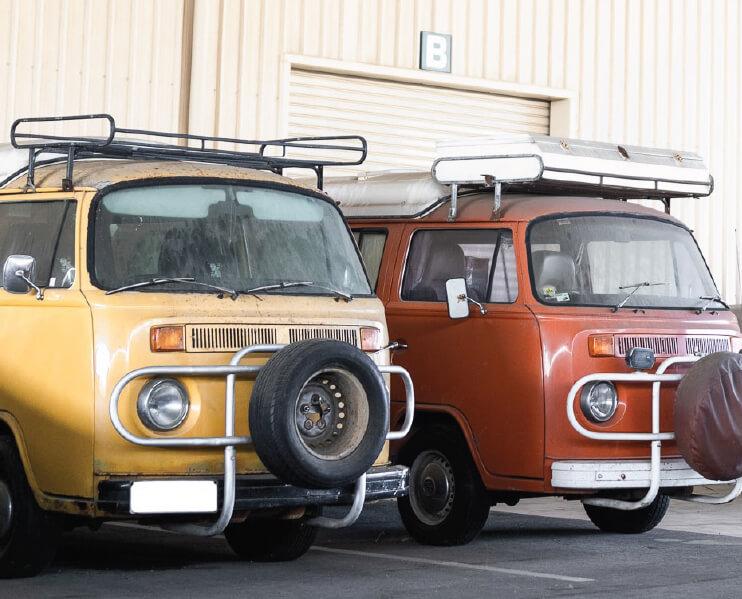 Two Volkswagen Kombi's outside